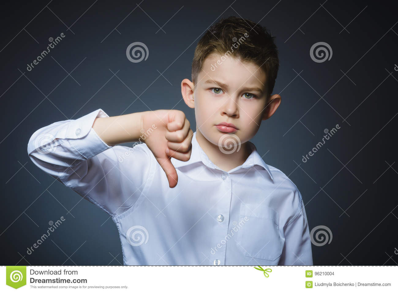Serious little boy holding his thumb down on gray background
