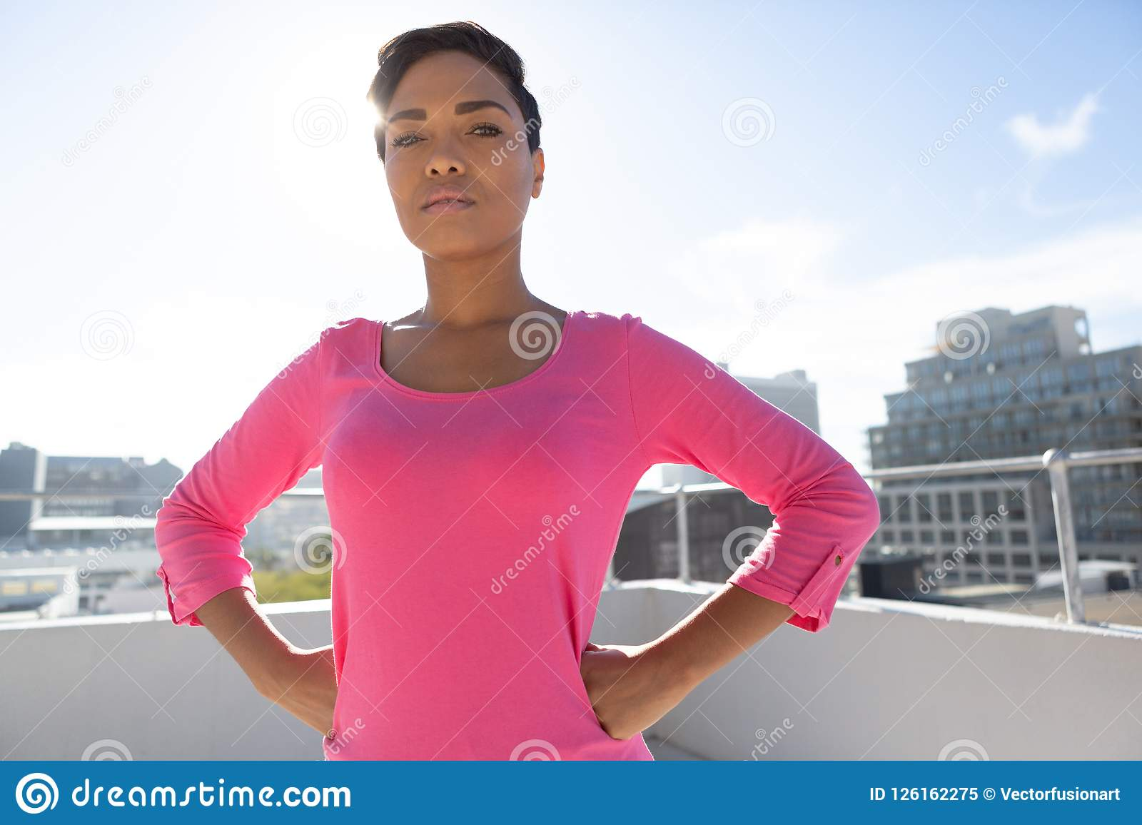 Serious looking woman standing confident for breast cancer awareness