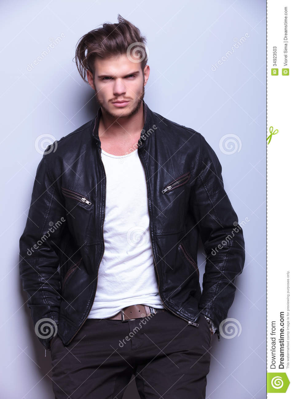 Serious Man In Leather Jacket Standing Against Gray Wall Stock ...