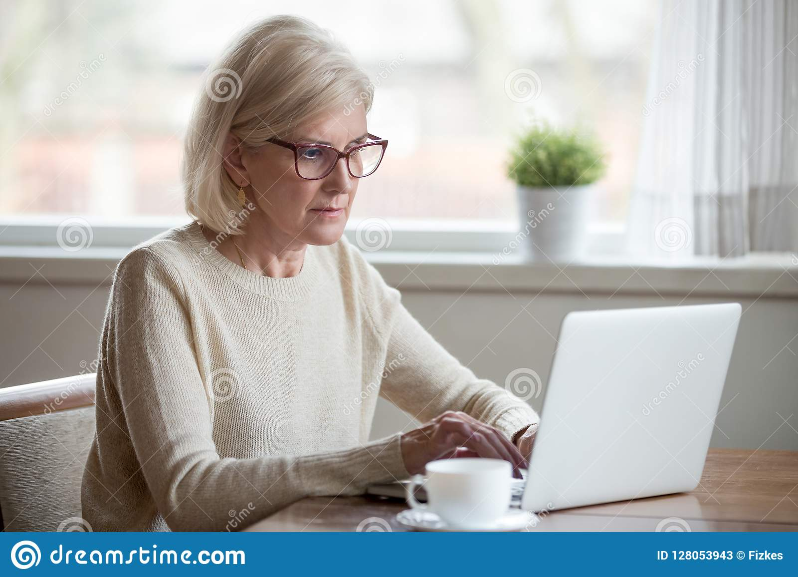 Serious mature middle aged business woman using laptop typing em