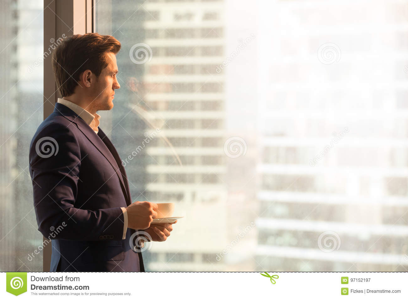 Serious pensive businessman drinking coffee, looking at sunrise