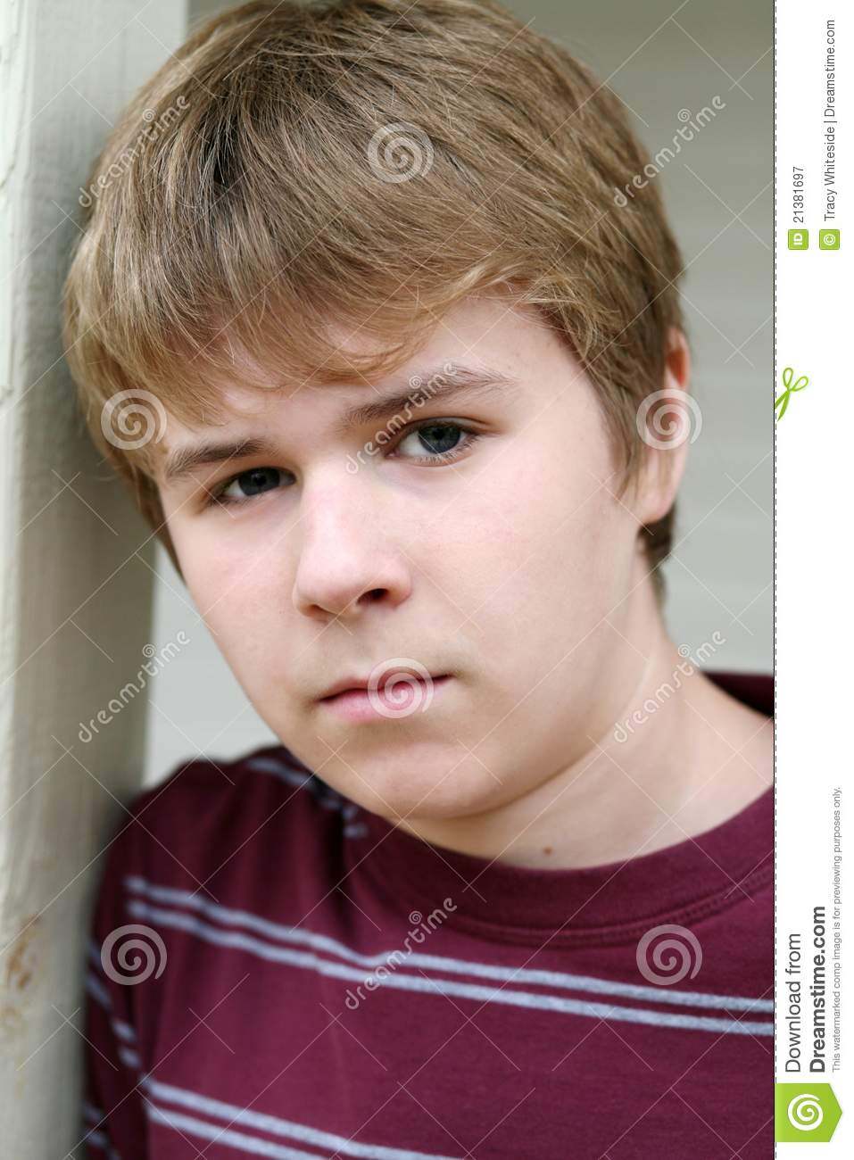 Closeup of cute young teen boy with serious expression.