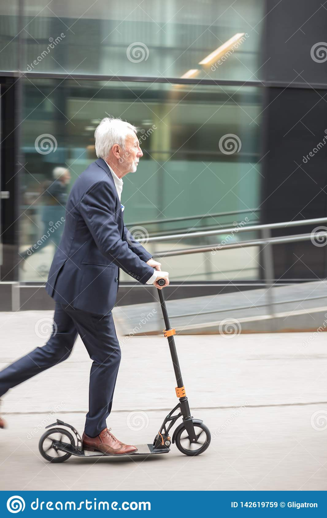 Serious senior businessman commuting to work on a push scooter