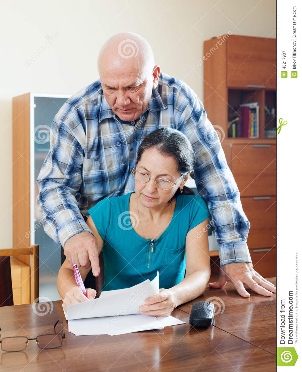 serious senior man with mature wife fills in questionnaire stock