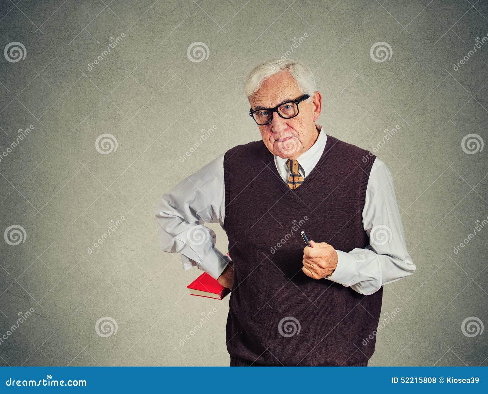 Serious senior strict teacher holding book and pen
