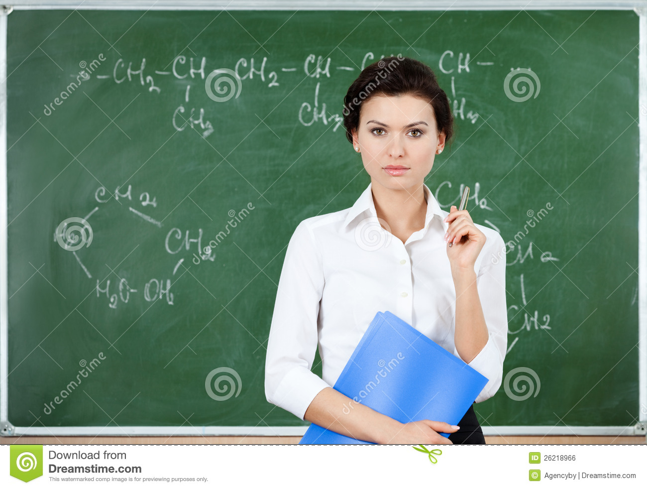 Serious Teacher Stands At The Blackboard Stock Photo