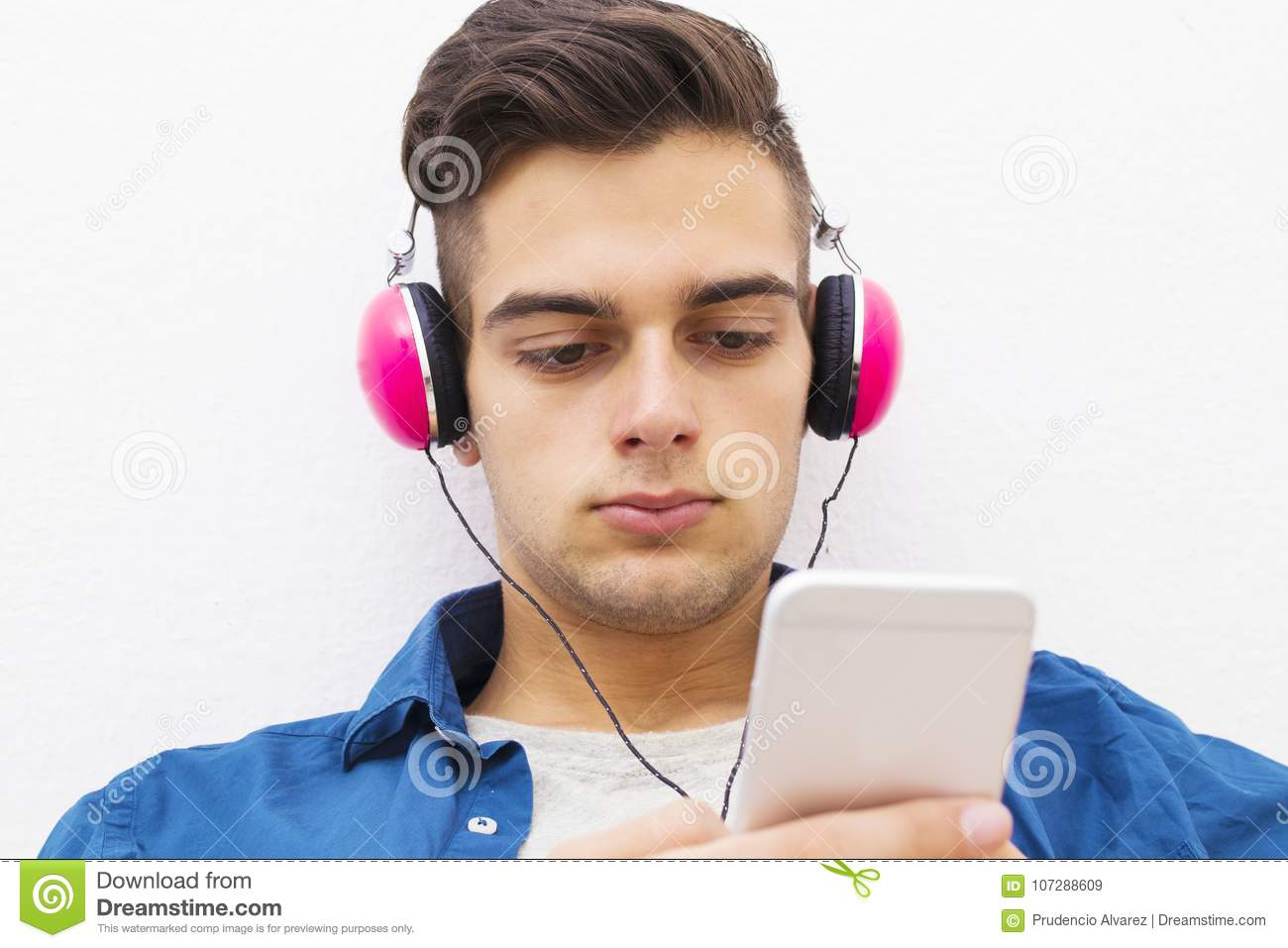 Serious teen boy with headphones and mobile phone
