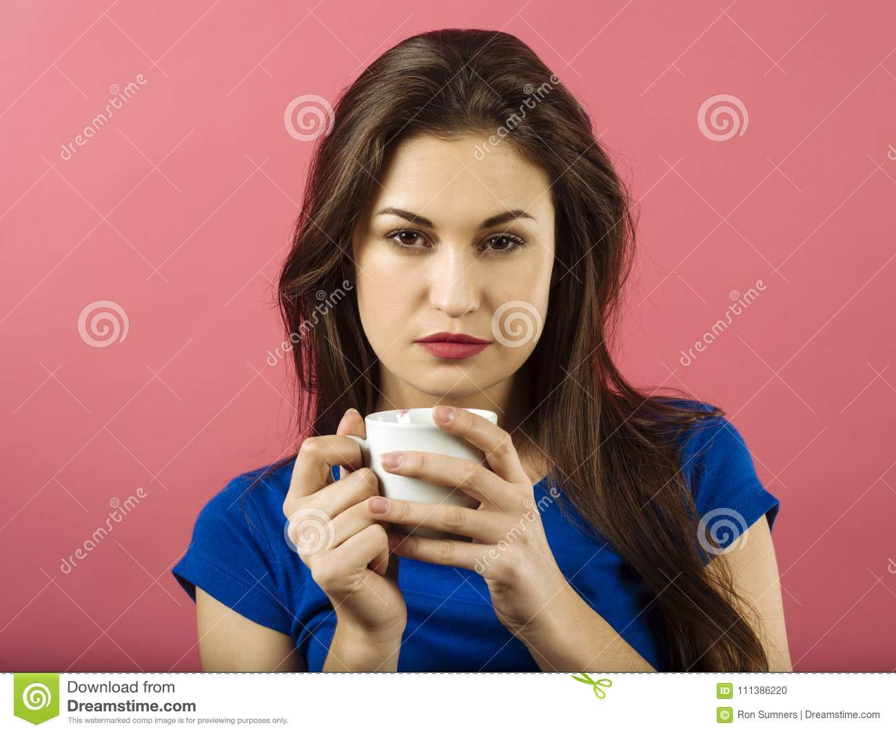 Serious woman drinking coffee over pink background