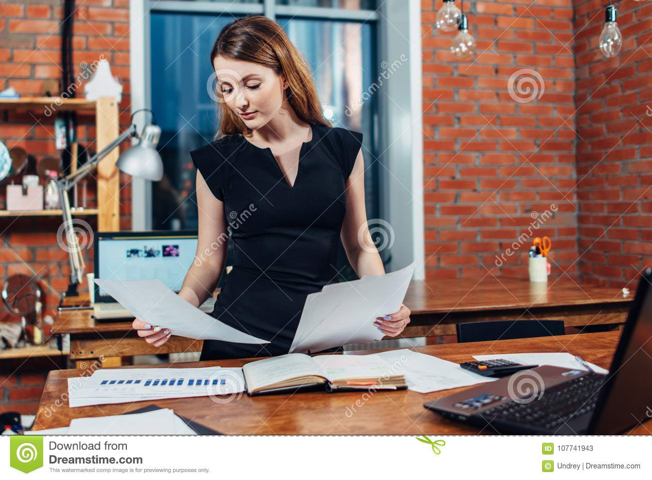 Download Serious Woman Reading Papers Studying Resumes Standing At Work Desk In Stylish Office Stock Image - Image of freelance, examining: 107741943