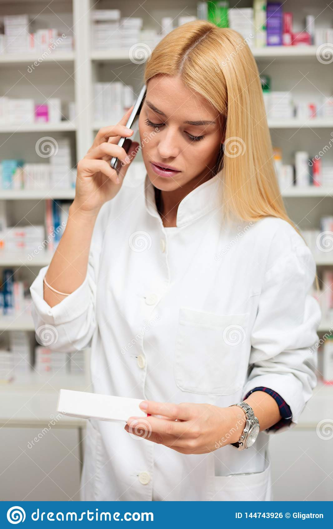 Serious young blond haired female pharmacist talking on the phone, holding a box of medications in other hand. Shelf with