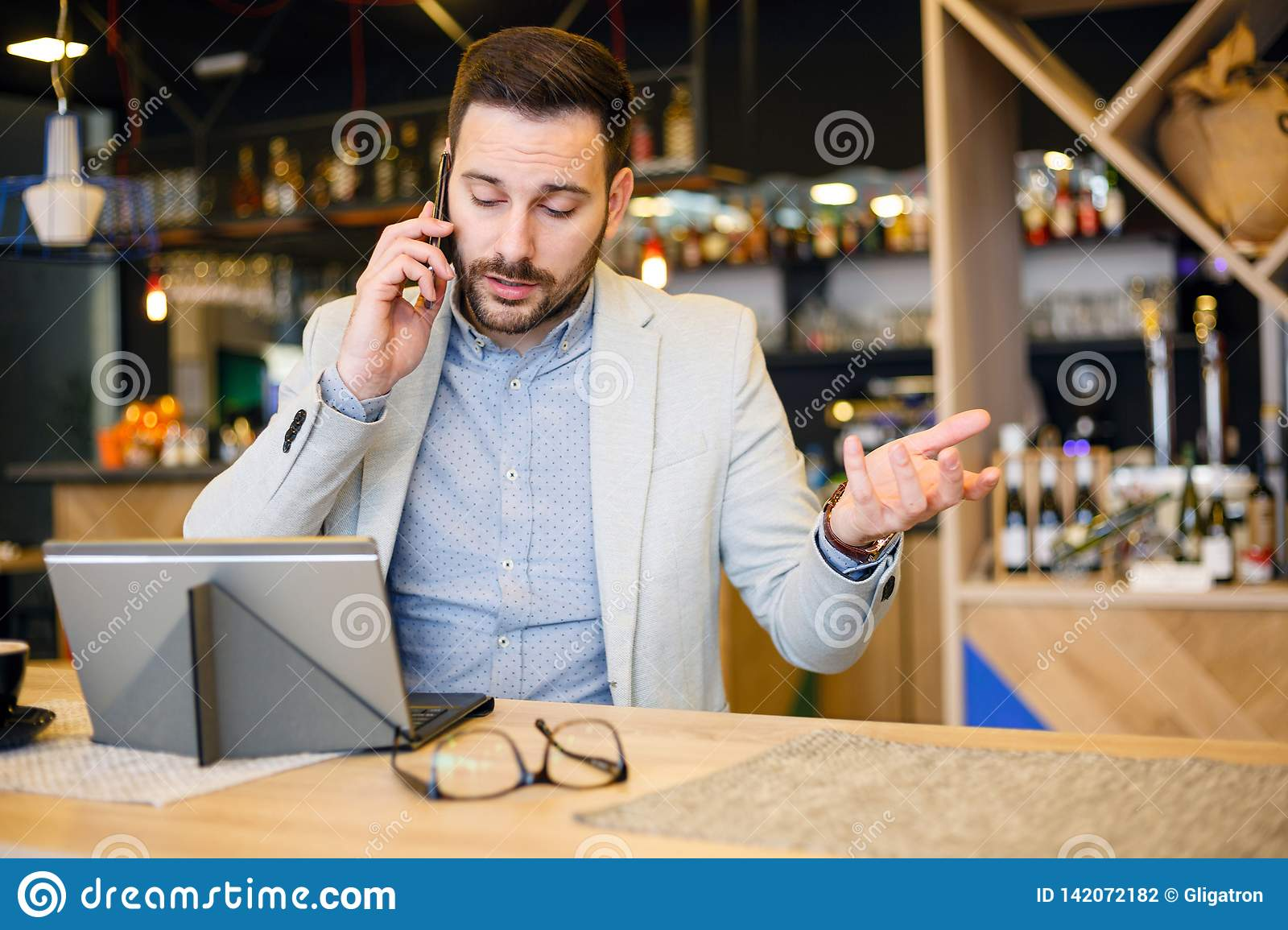 Serious young businessman talking on a phone, working in a cafe