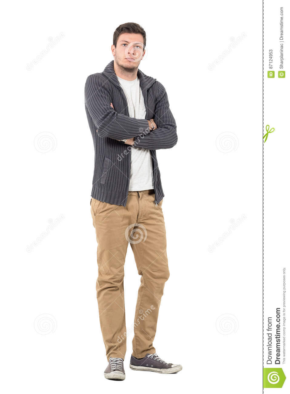 873043fb0b Serious young casual man in unzipped sweater with crossed arms looking at  camera.