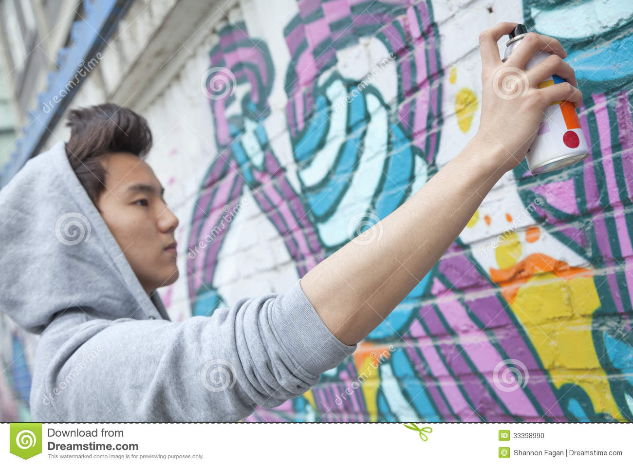 Serious young man concentrating while holding a spray can for Wall spray painting designs