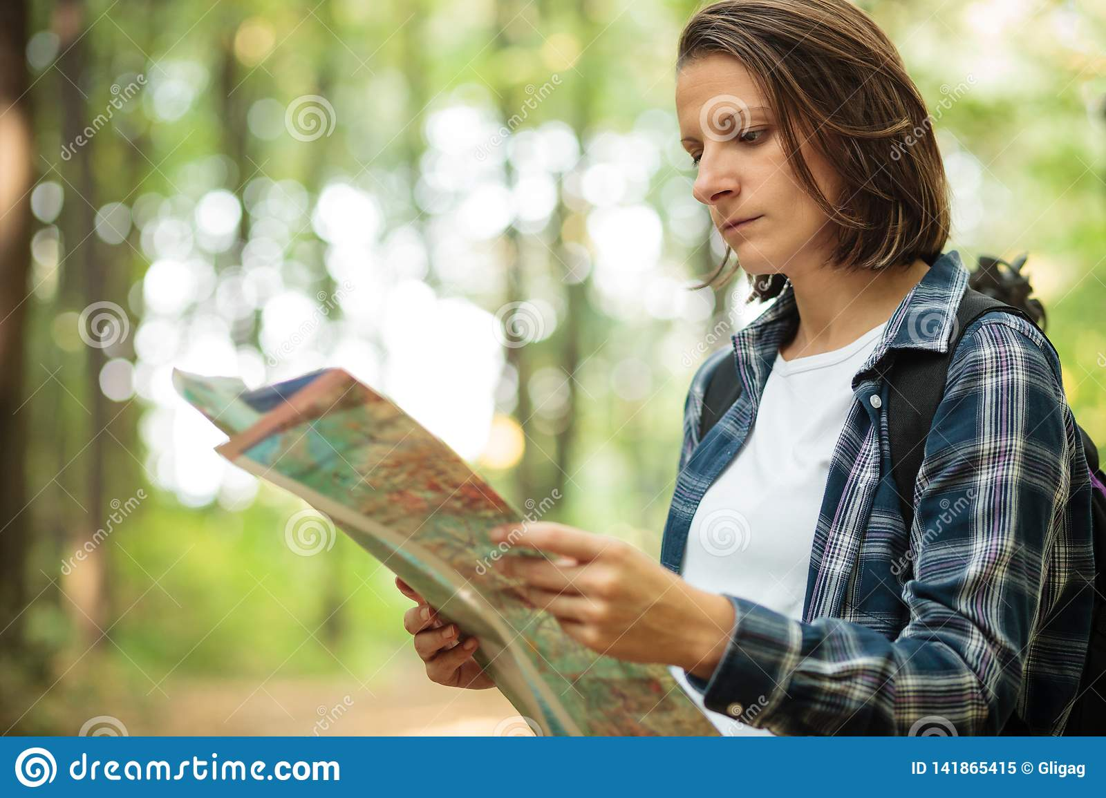 Serious young woman looking at the map and navigating while hiking through lush green forest