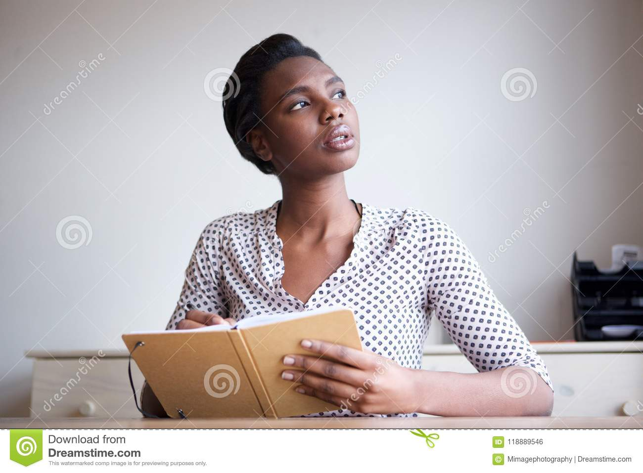 serious young woman thinking and writing in journal stock photo