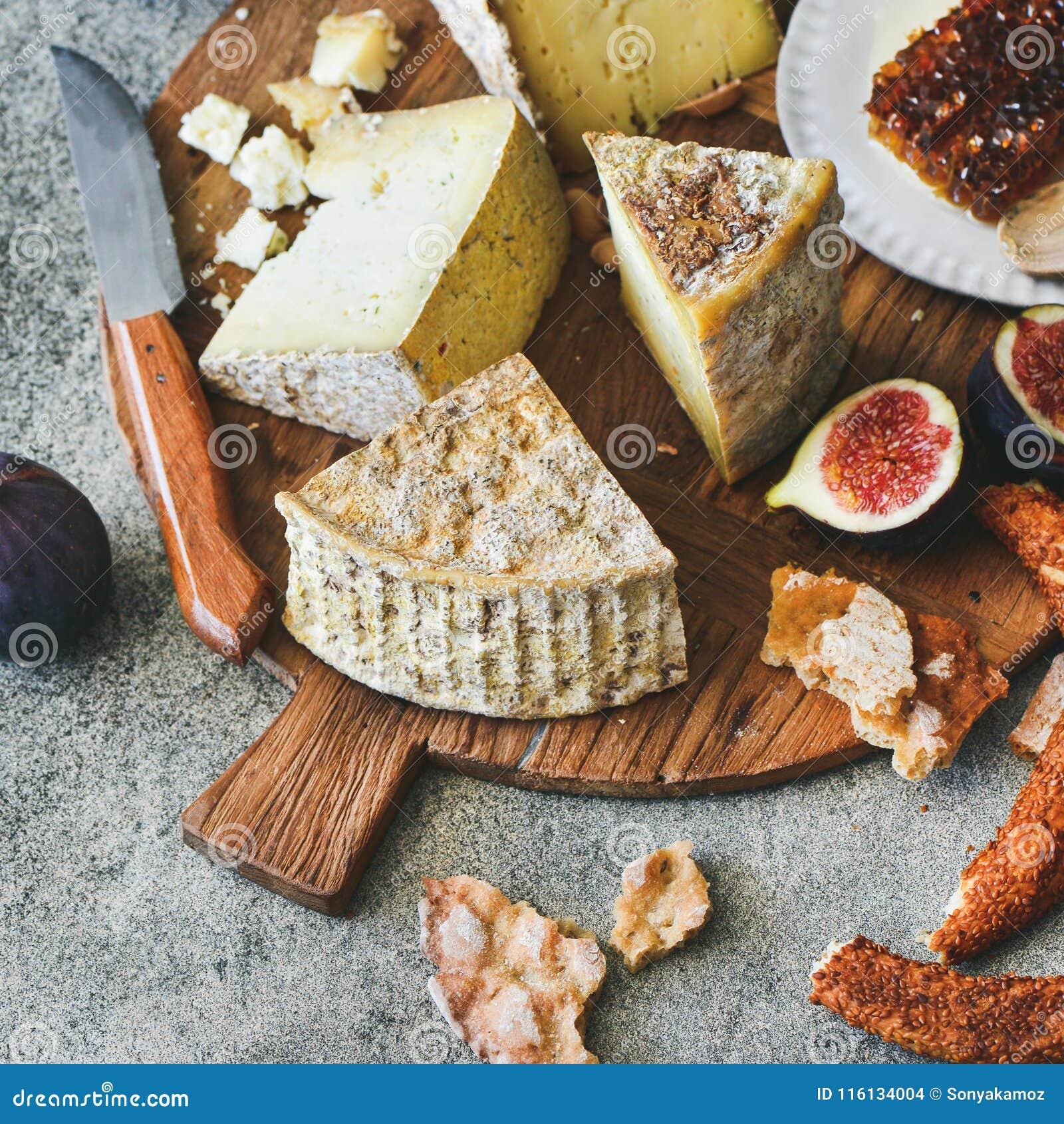 Serowy asortyment, figi, miód, świeży chleb i dokrętki, kwadratowa uprawa