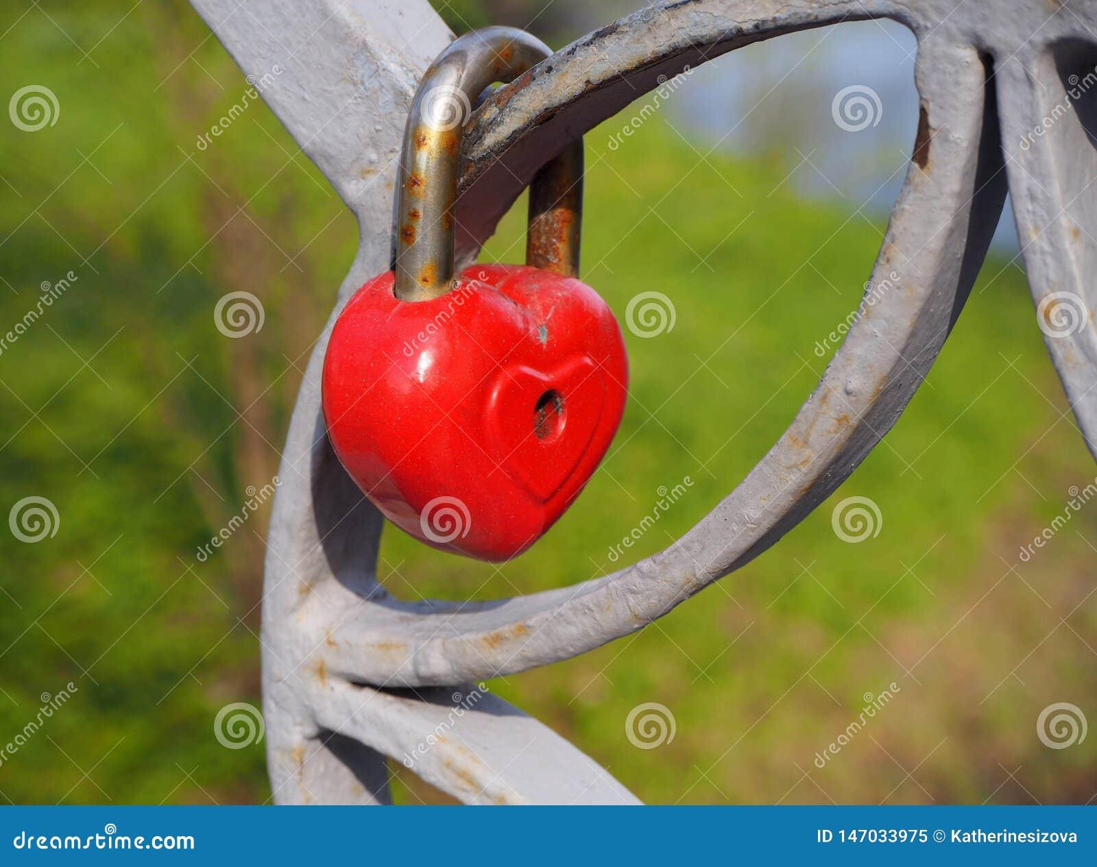 Serrure rouge de coeur vieil en m?tal rouill?, le symbole romantique de l amour interminable accrochant sur la barri?re du pont