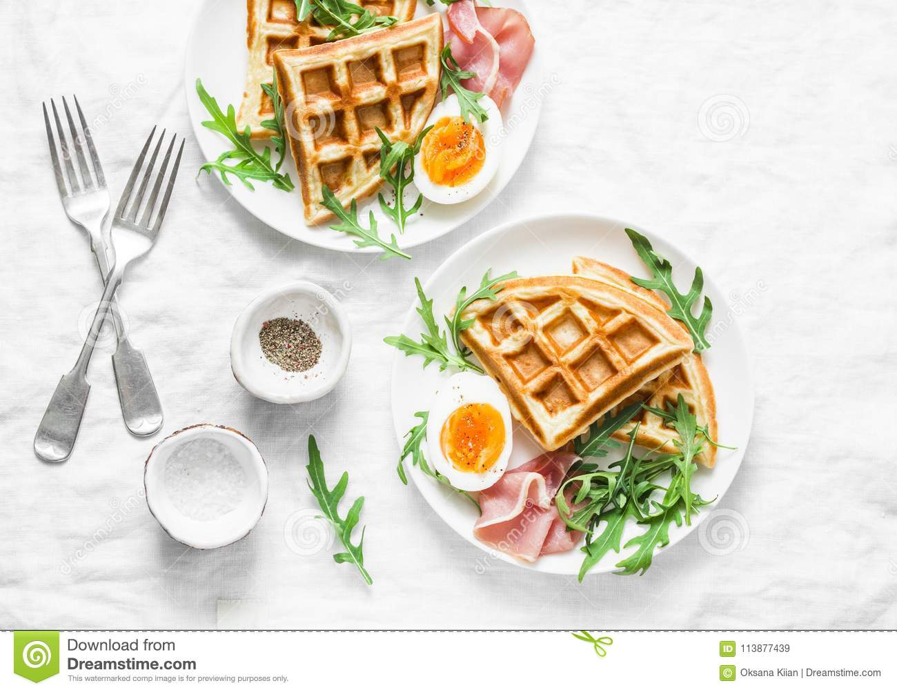 Served breakfast with potatoes savory waffles, boiled egg, ham and arugula on light background, top view. Appetizers, snack, brunc