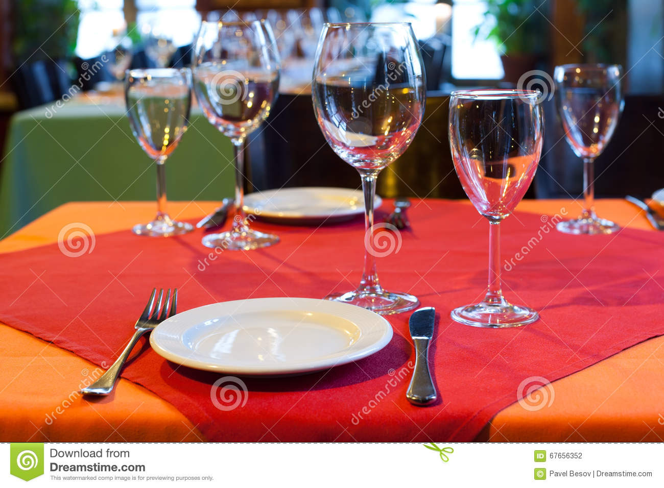 Served table in restaurant. white plate knife fork and wine glasses on red napkin. romantic interior concept