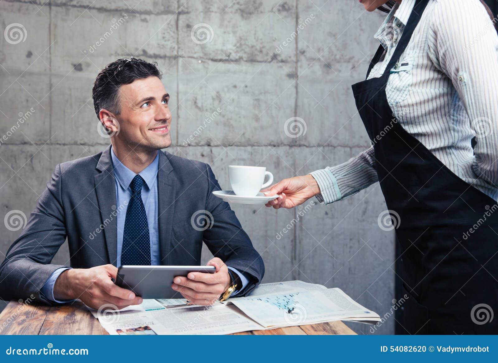 Serveerster die kop met koffie geven aan de mens