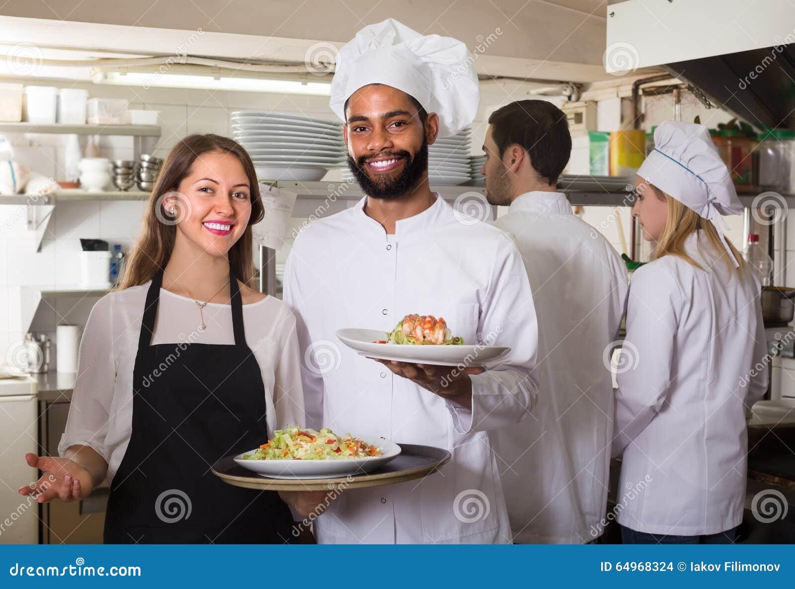 Serveerster en bemanning van professionele koks die bij restaurant stellen