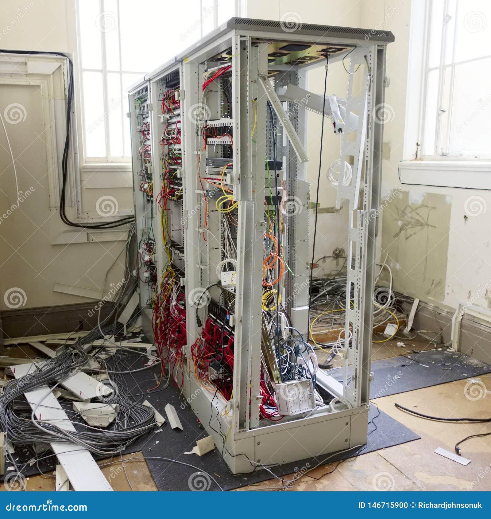 Serverrahmen-Hardware-Gestell und lose Kabel in der Nachrichtenzentrale entfernt im aufgegebenen Bürogebäude