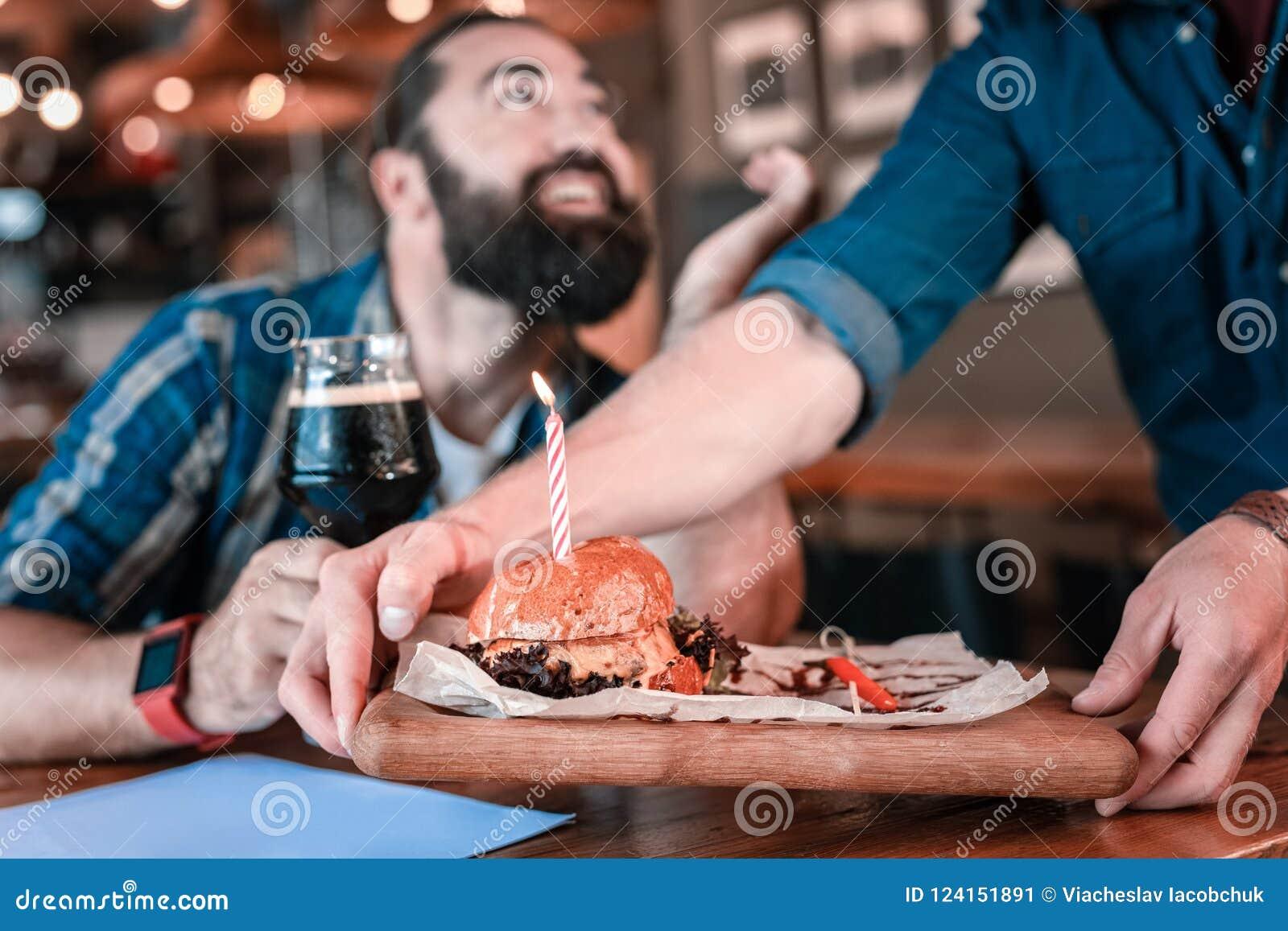 Serveur agréable saumurant l hamburger bon de viande avec peu de bougie d anniversaire