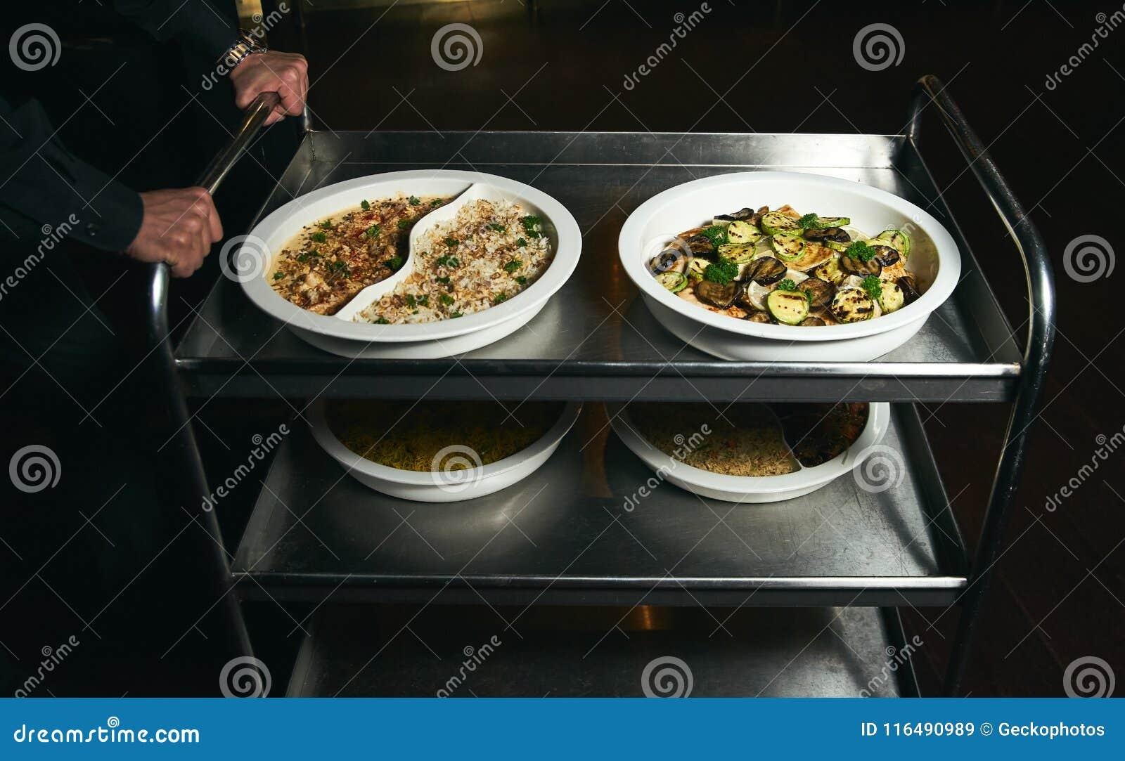 Serveur avec un chariot de portion de nourriture à un restaurant végétarien