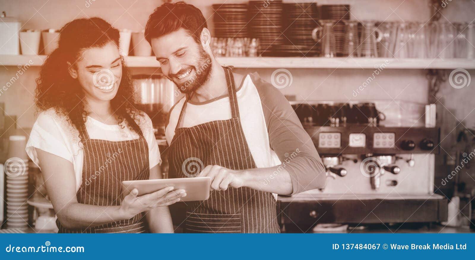 Serveur et serveuse de sourire à l aide du comprimé numérique au compteur
