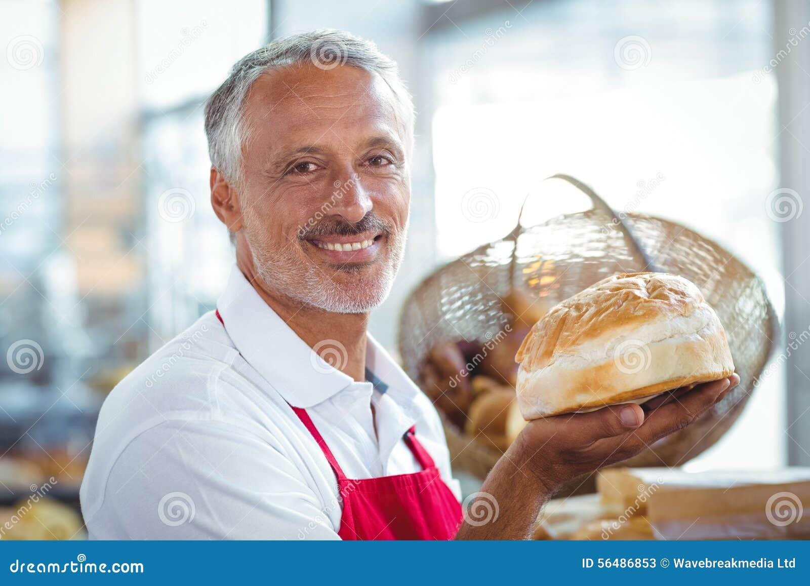 Serveur regardant l appareil-photo et tenant le pain fraîchement cuit au four