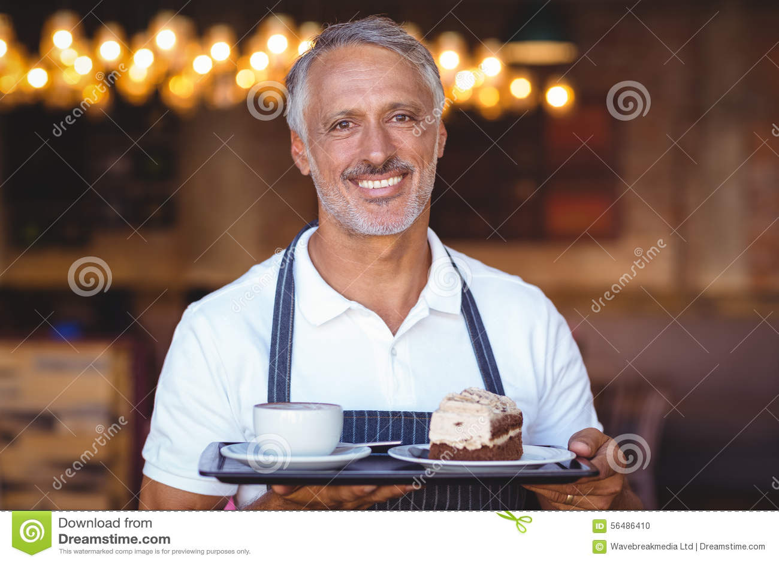 Serveur souriant et tenant le plateau