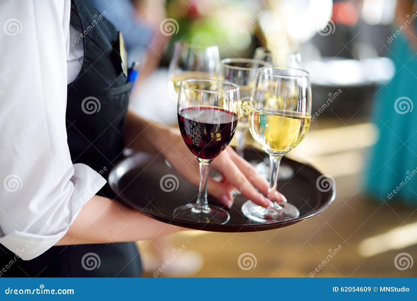 Serveuse avec le plat des verres de champagne et de vin