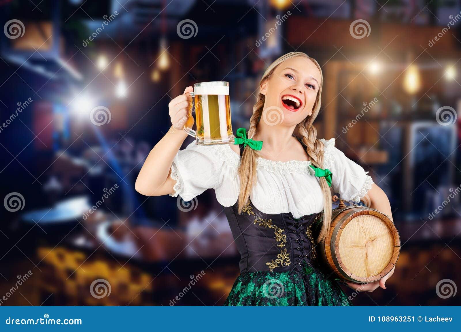 Serveuse de jeune fille oktoberfest dans le costume national avec une tasse o