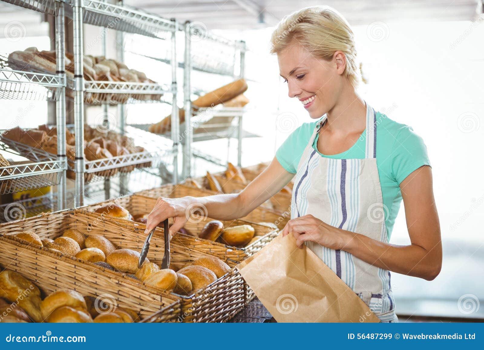 Serveuse de sourire posant le prochain panier du pain