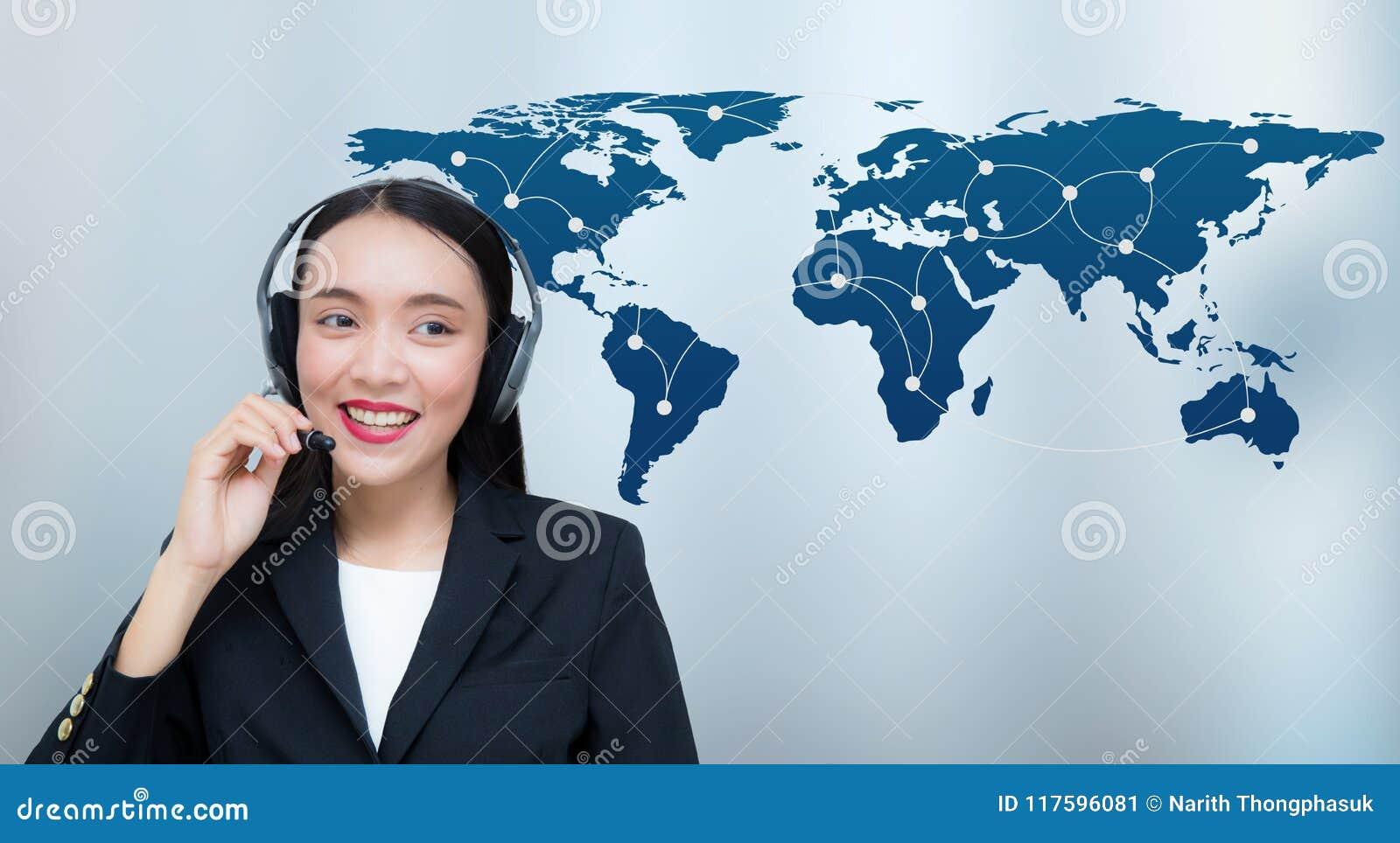 Serviço ao cliente de sorriso da mulher asiática bonita que fala em auriculares com uma comunicação do mapa do mundo