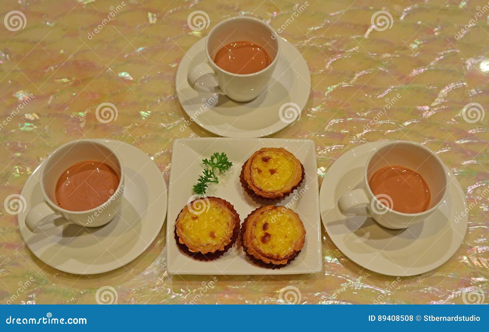 Serviço da sobremesa do dim sum da mini galdéria recentemente cozida do ovo e do chá perfumado do leite