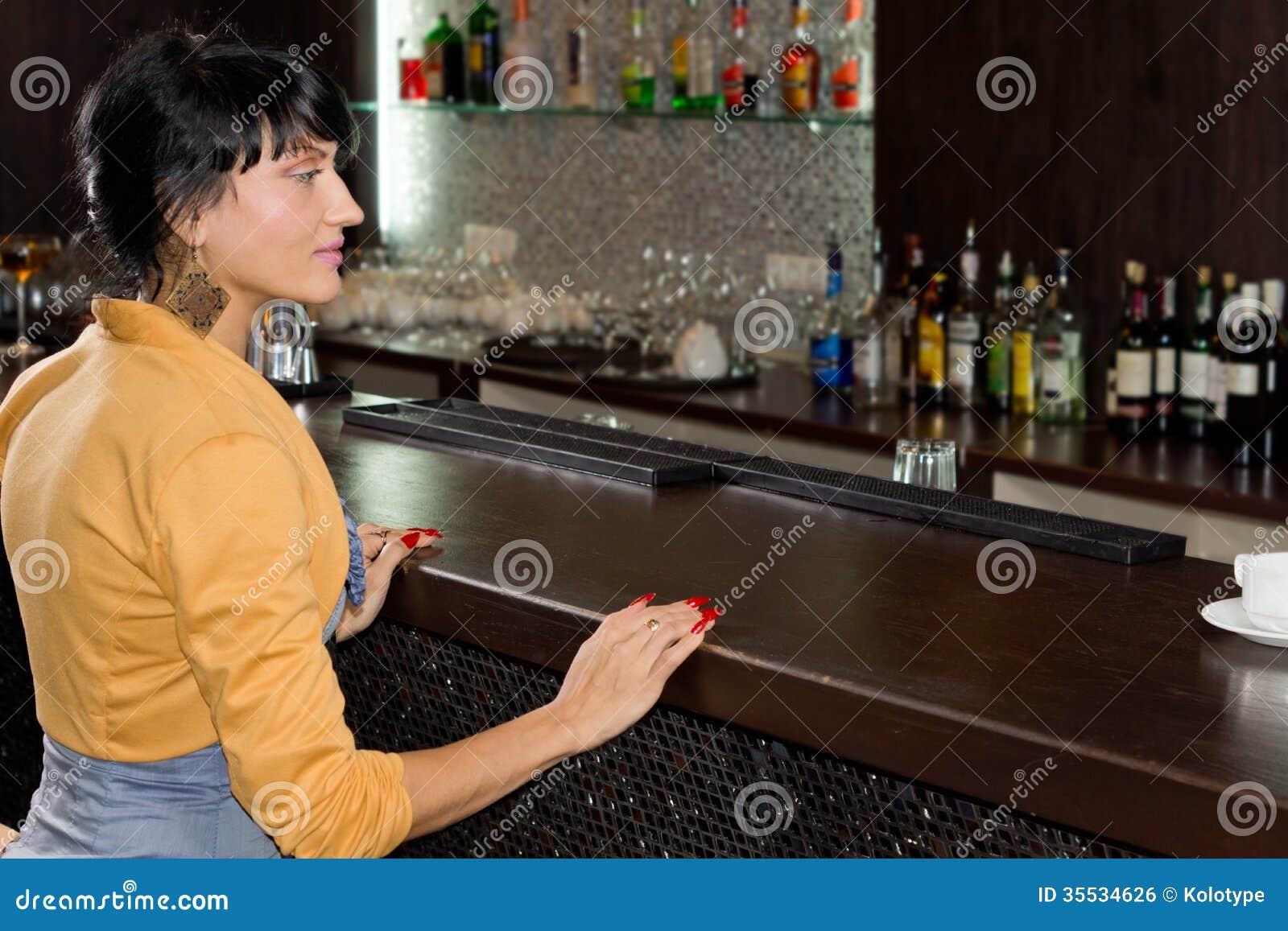 Serviço de espera da jovem mulher no contador da barra