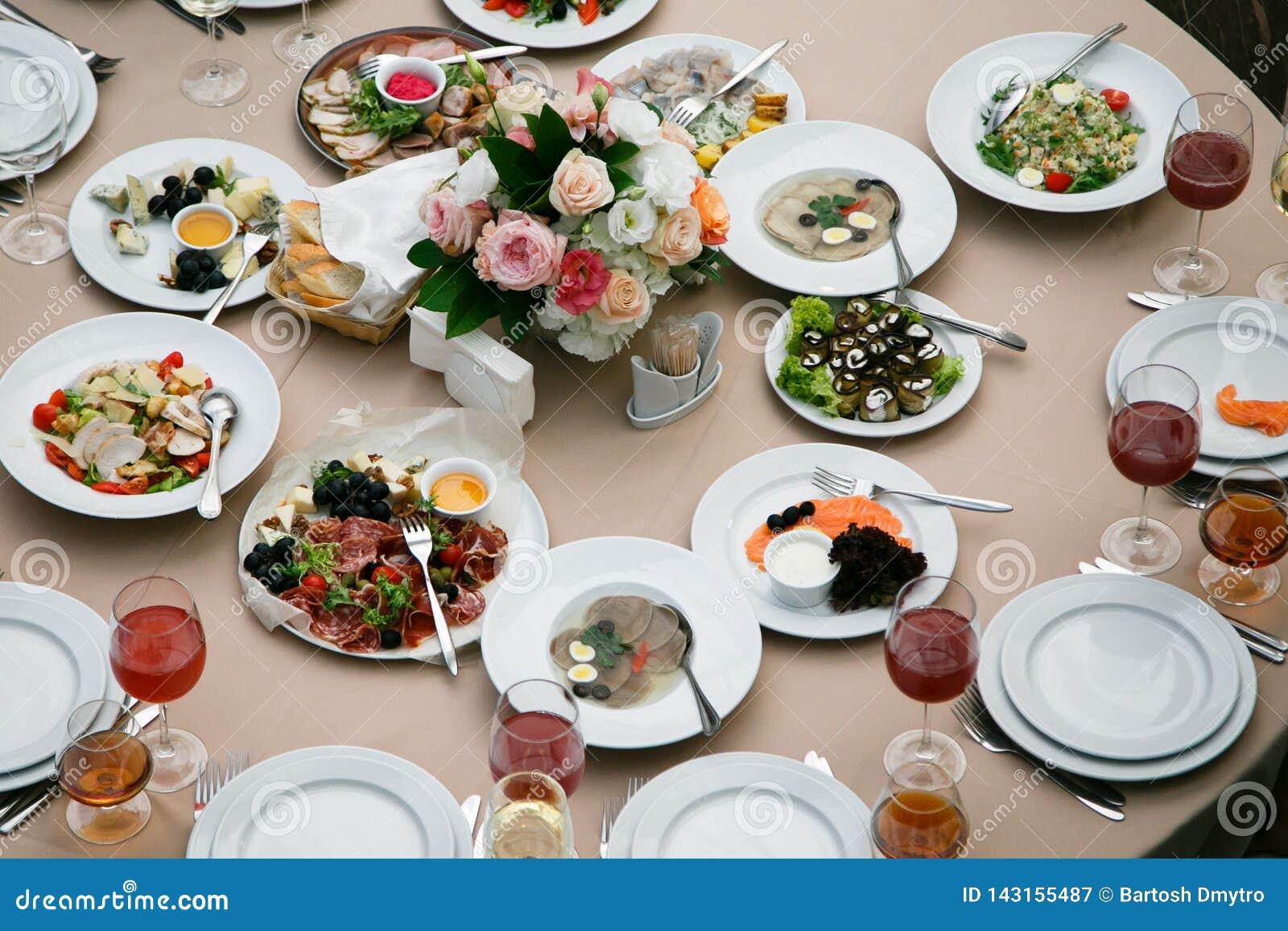 Servi à la table de restaurant de banquet avec des verres de plats, de casse-croûte, de couverts, de vin et d eau, nourriture eur