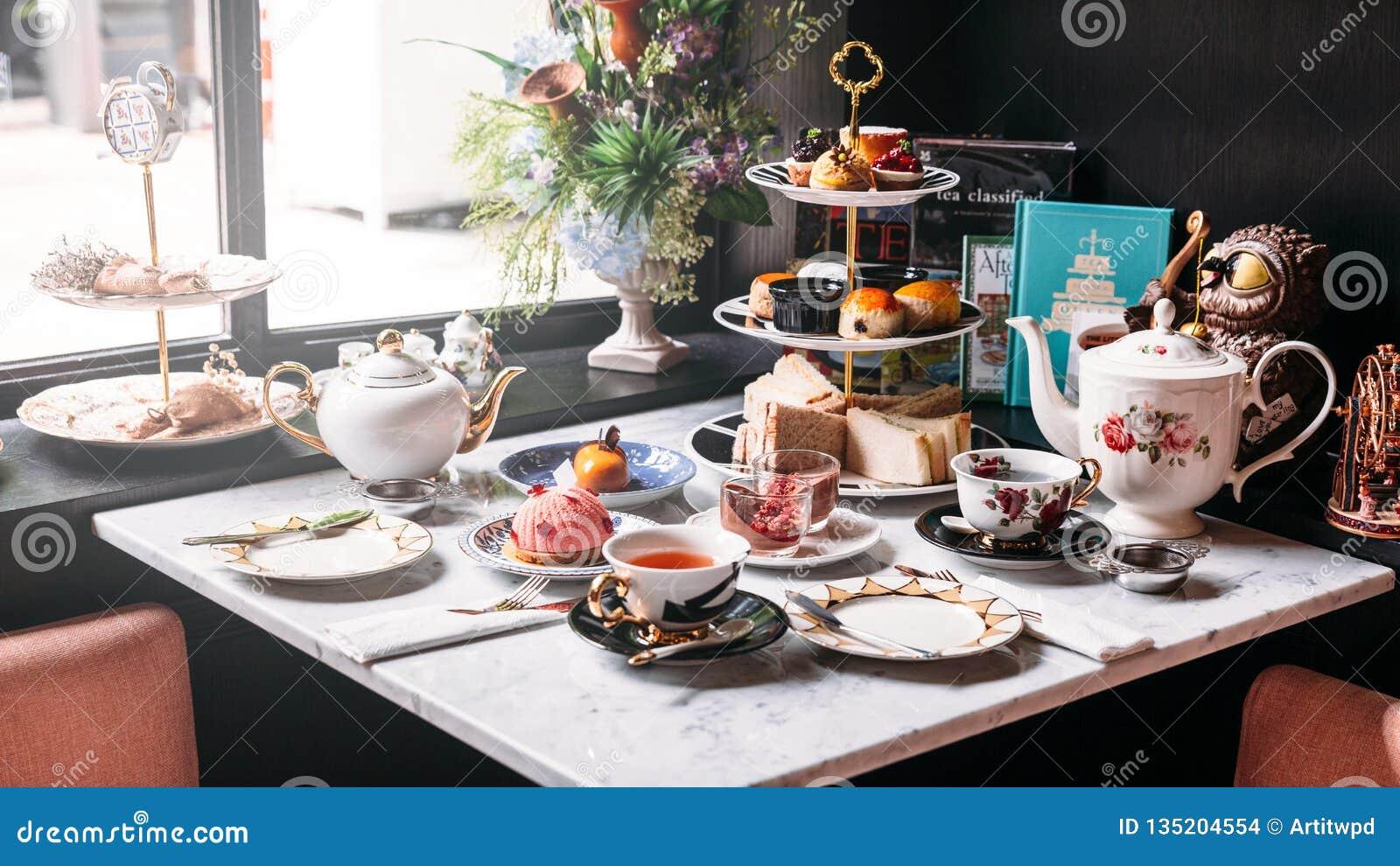 Service à thé anglais d après-midi comprenant le thé chaud, la pâtisserie, les scones, les sandwichs et les mini tartes sur la ta