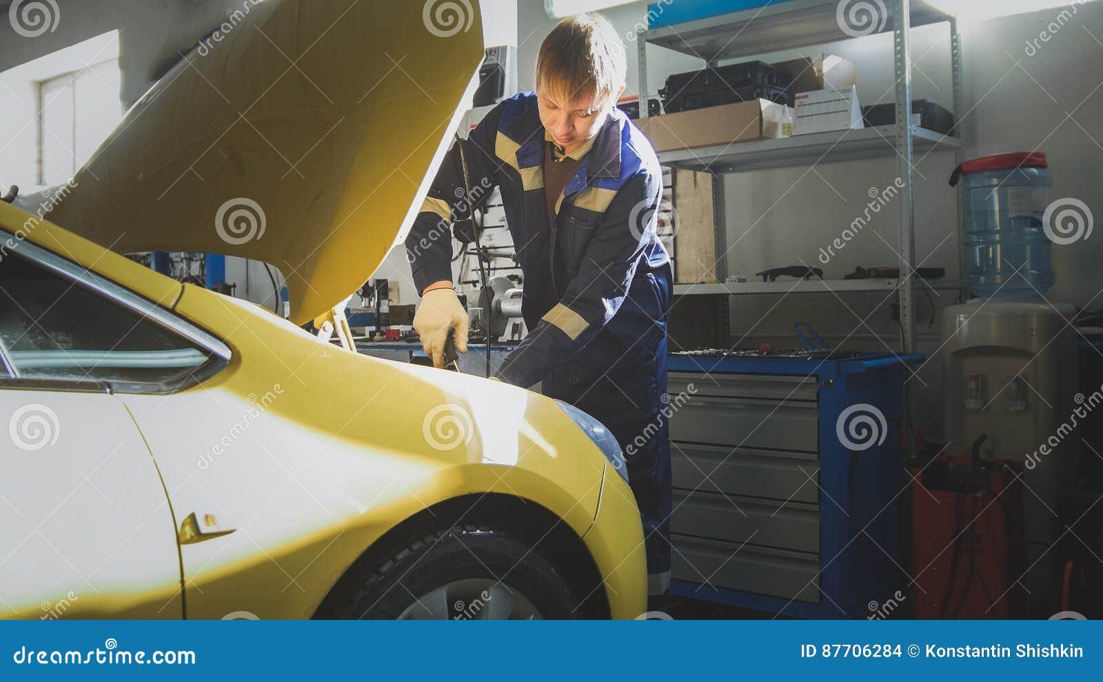Service d automobile - le mécanicien dévisse le détail de la voiture dans le capot, glisseur