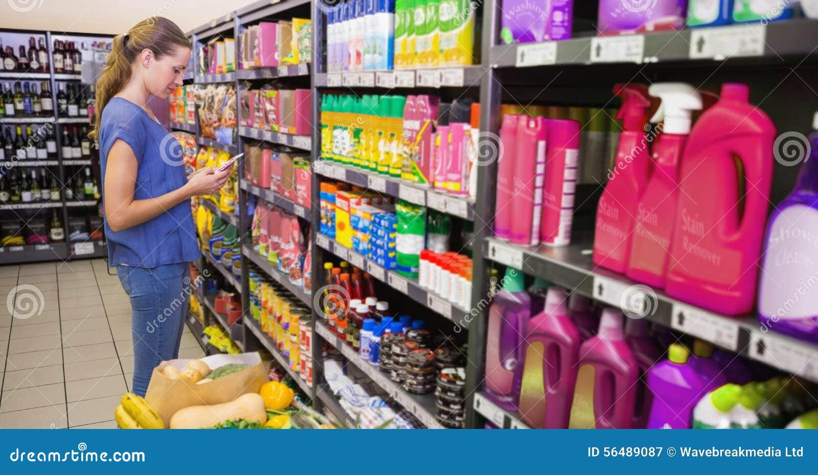 Service de mini-messages de femme devant l étagère de produit