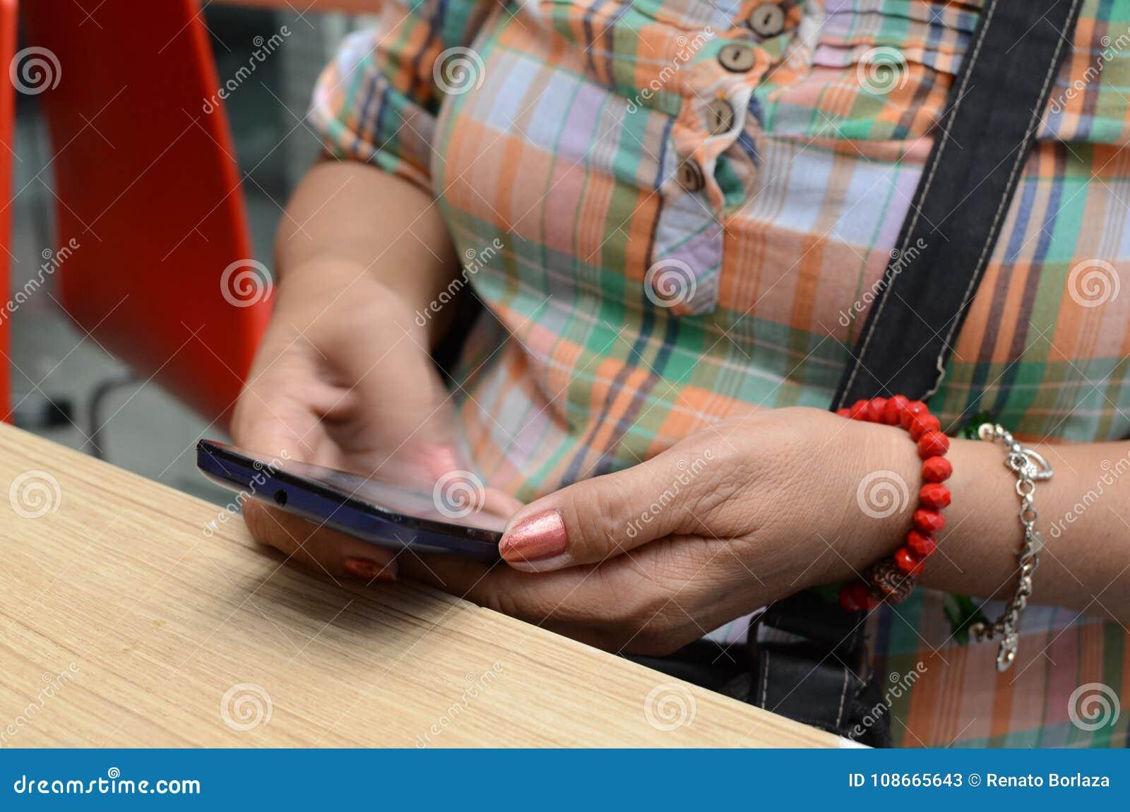 Service de mini-messages mûr de main du ` s de femme sur le smartphone au restaurant
