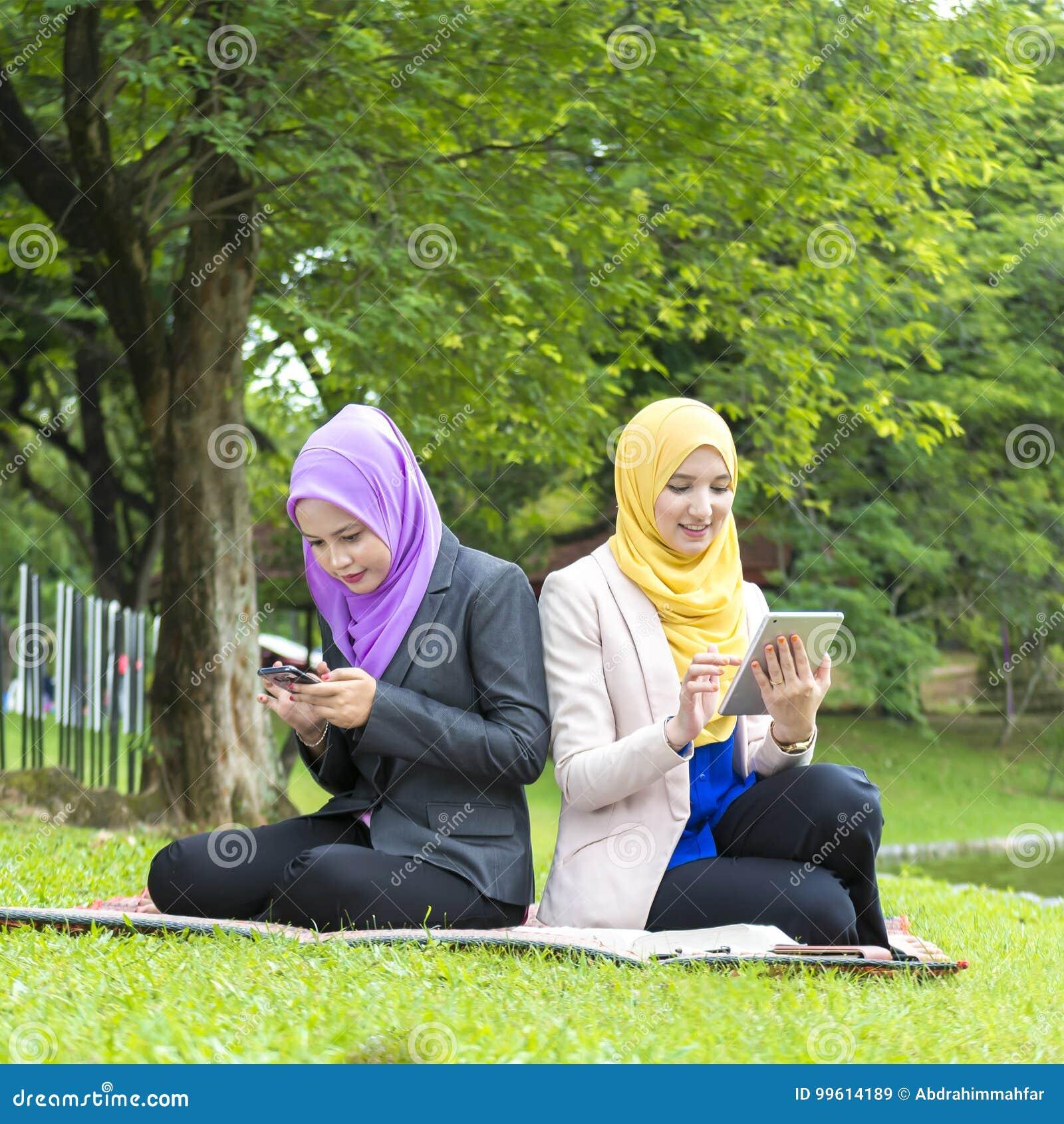 Service de mini-messages occupé de deux étudiants universitaires avec leur smartphone tout en se reposant en parc