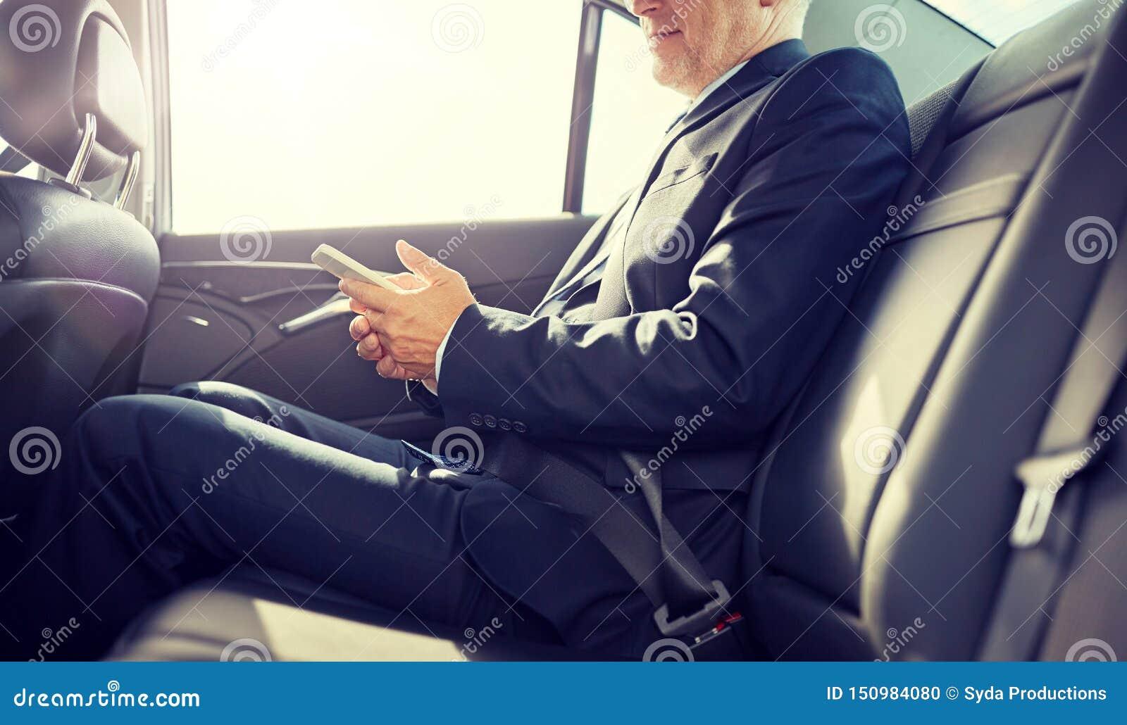 Service de mini-messages sup?rieur d homme d affaires sur le smartphone dans la voiture