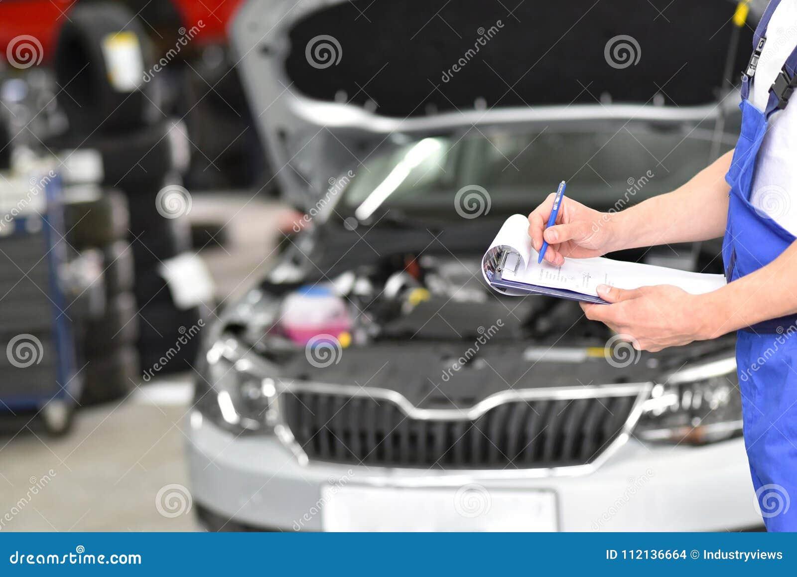 Service et inspection d une voiture dans un atelier - le mécanicien inspectent