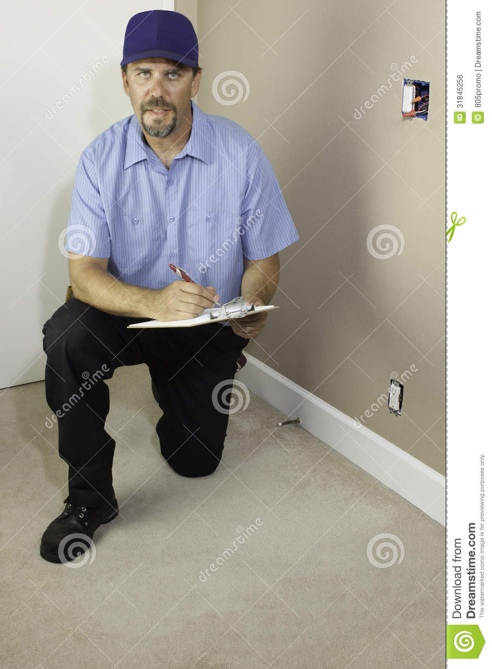 Service Man Kneeling With Clipboard Royalty Free Stock