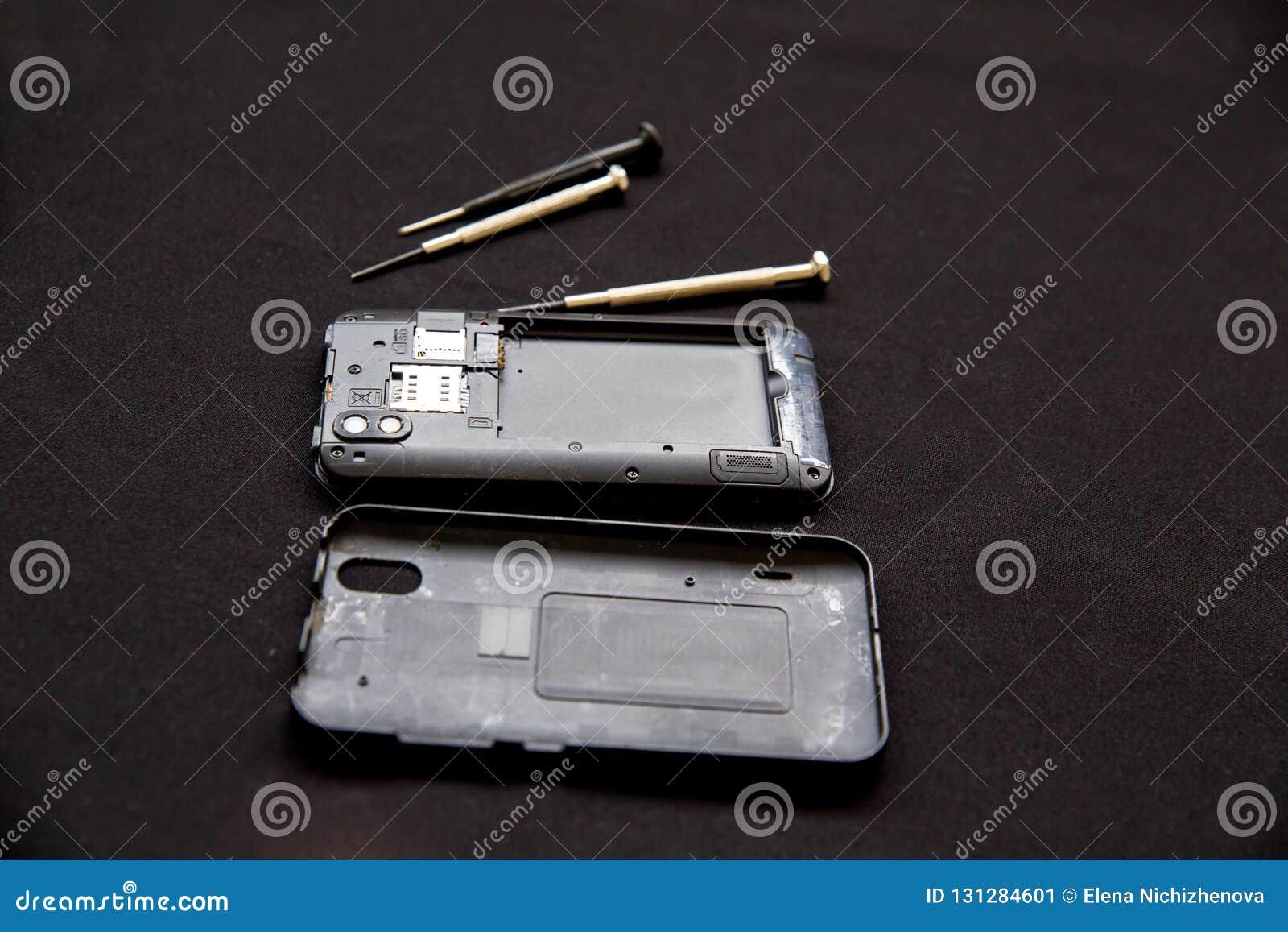 Servicio de reparación de la electrónica - el técnico está fijando el teléfono celular quebrado