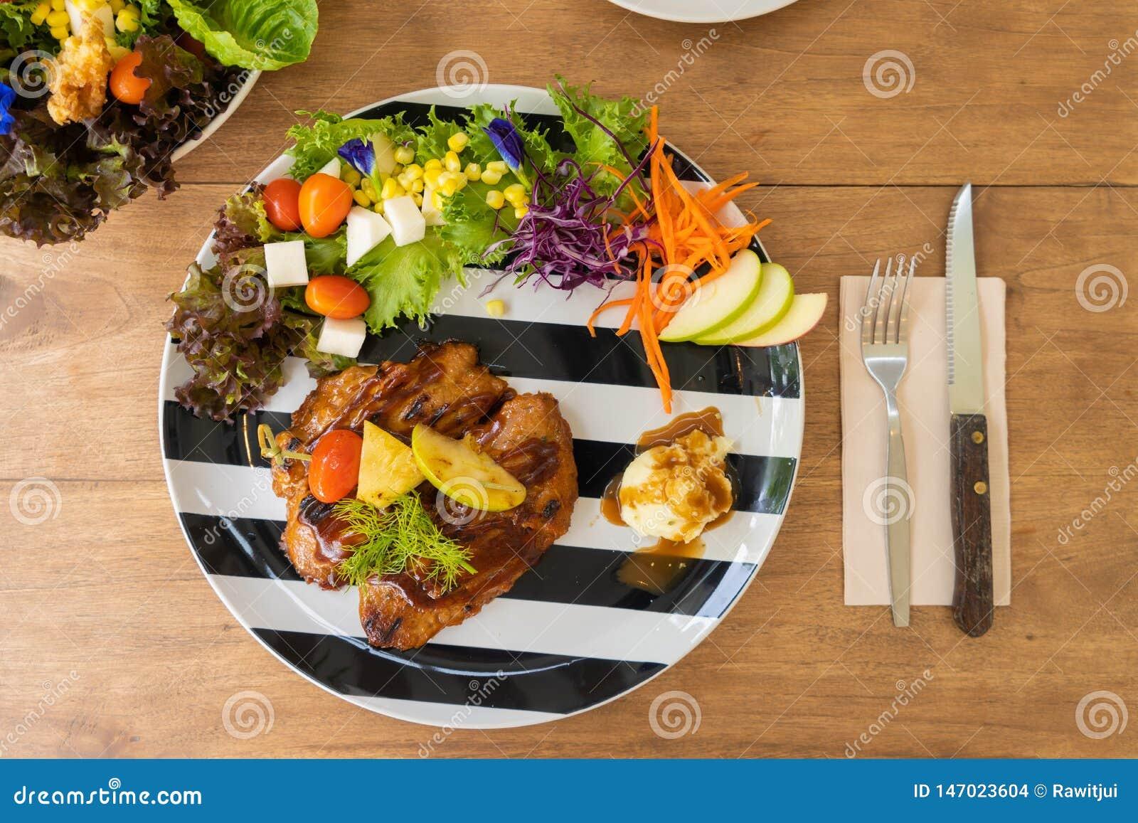 Servicio del filete del pollo con el puré de patata y la ensalada en una placa blanco y negro en una tabla de madera