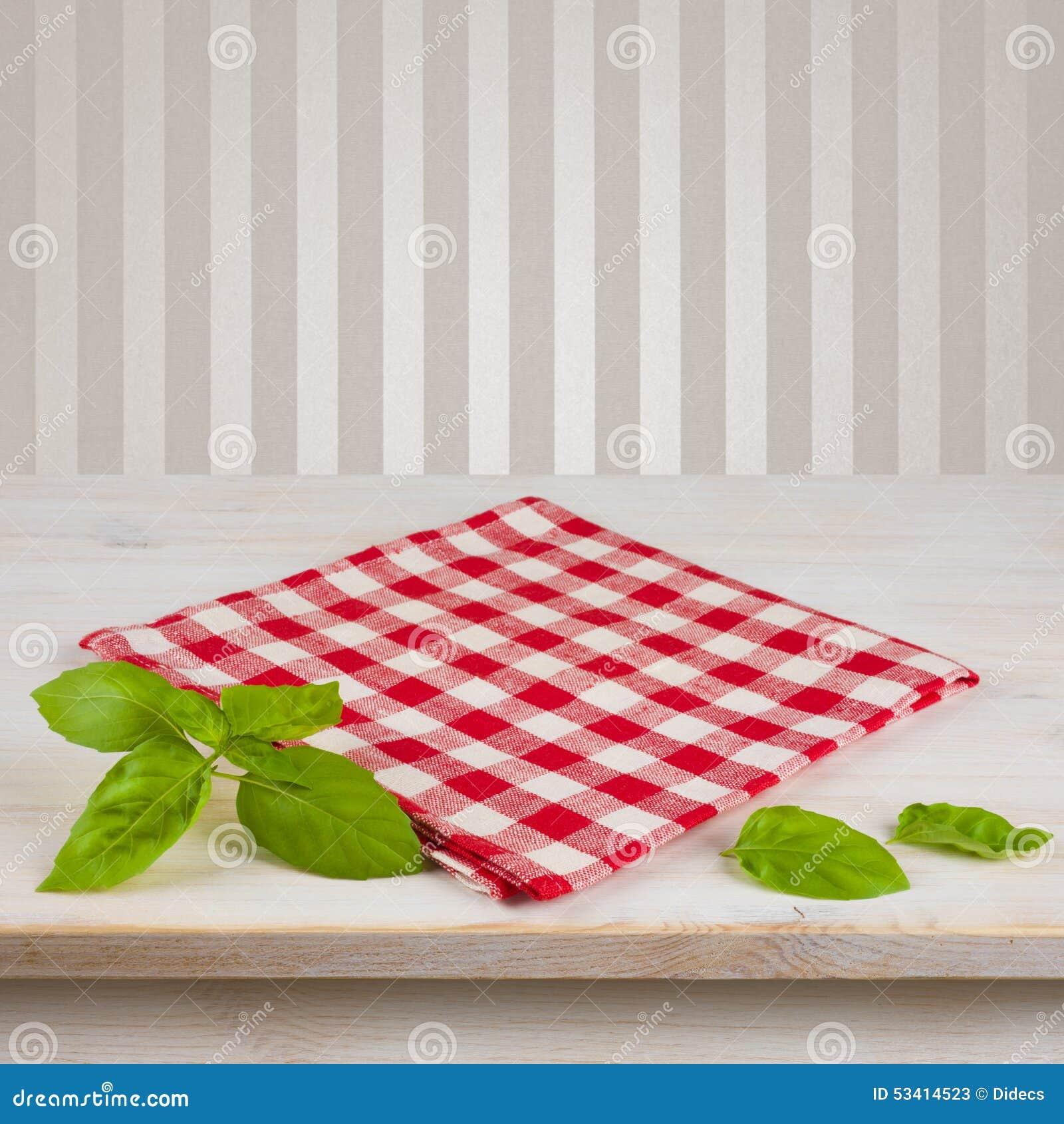 Serviette et feuilles à carreaux rouges sur la table au-dessus du fond de vintage