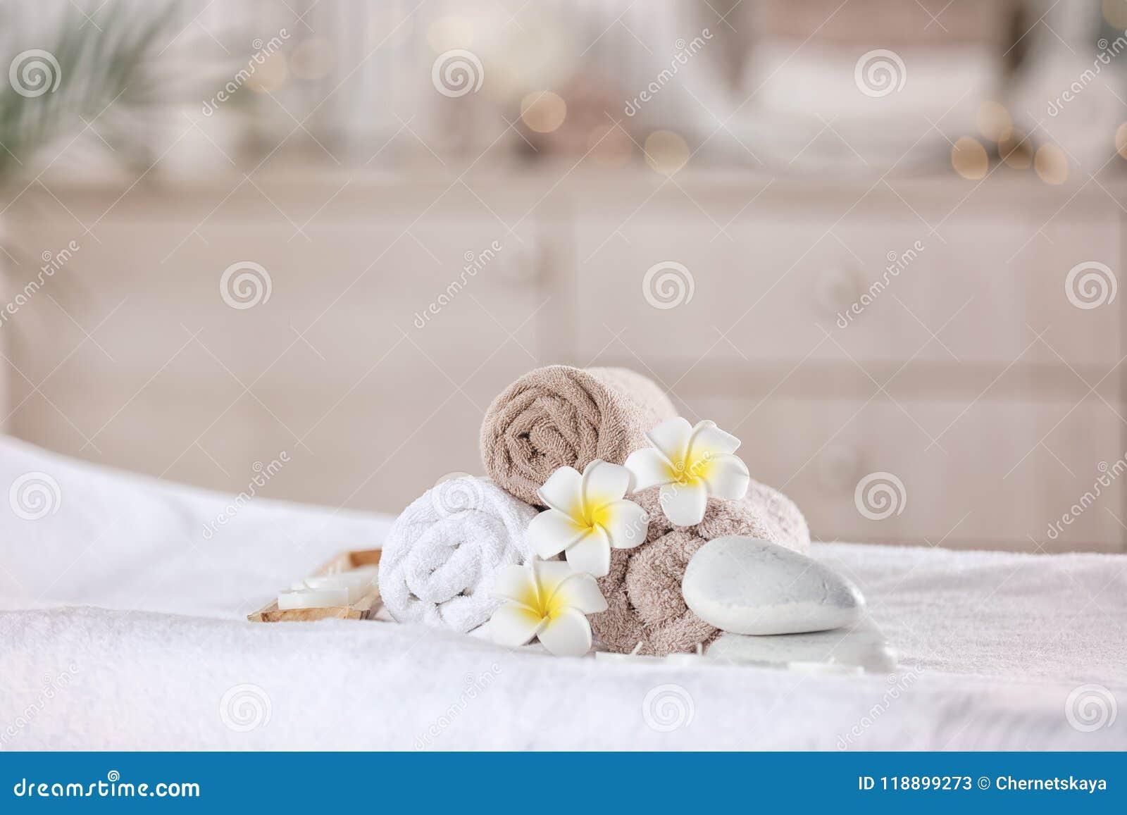 Serviettes et bougies sur la table de massage dans le salon moderne de station thermale Place pour la relaxation